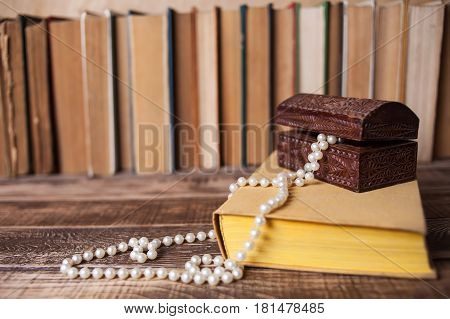 Books on the wooden table, bead in casket on the book