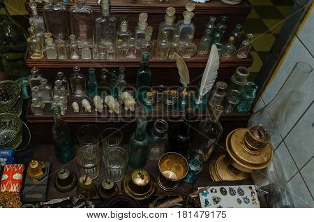 Moscow, Russia - March 19, 2017: Table at the flea market with empty antique bottles and flacons for alcohol, medicines and perfumes of various sizes and colors