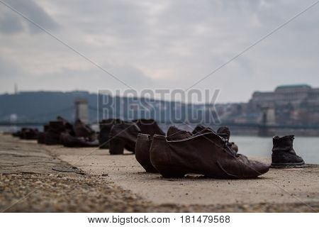 These shoes are a memorial to honour Jews killed by fascist Arrow Cross militiamen in Budapest during World War II. They were ordered to remove their shows & were shot on the river bank. Their bodies fell into the water & only their shoes remained. Chain