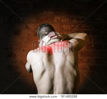 A man with a sore neck in the bus Trench stands with his back against the bricks wall
