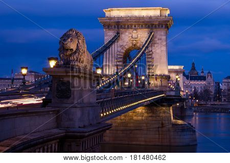 One of the four lion statues on the end of Chain Bridge in Budapest. The iconic suspension bridge looked at it's best lit up against the fading blue colours of the night.