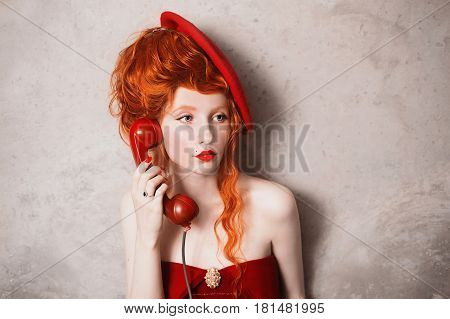 Redhead curly girl in a red beret her lips smeared red lipstick and holding a disk telephone. A woman in a red dress on a gray background. Retro lady. Photo in theater actress with red telephone. Retro film. Art photo. Red dial telephone. Talking on the t