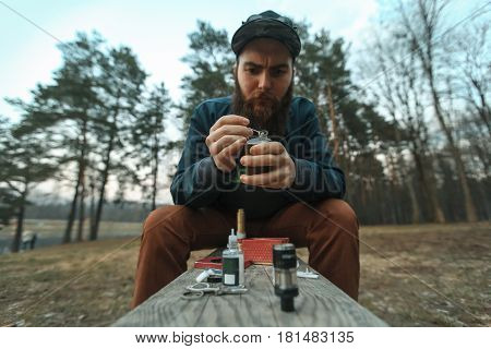 Vape. Young Man With Large Beard In A Cap Stows Cotton Into An Electronic Cigarette.