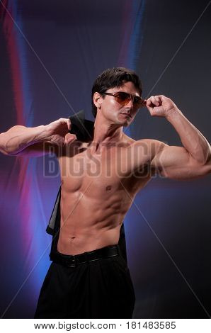 the sexy man is holding his glasses.