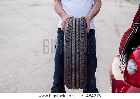 Car remained out of order on the road the driver pulls the spare tire out of the trunk to be replaced