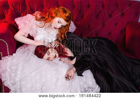 Two gorgeous girls with red hair in retro dress in the bedroom. Femme fatale in a black gorgeous dress and nice girl in white wedding dress. Fairy and Witch. Model posing in studio. Historical renaissance gorgeous dresses. Gorgeous model