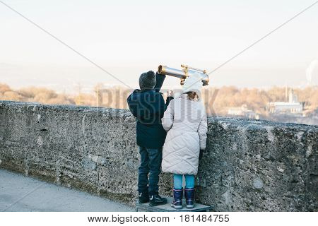 Children (boy and girl) look through the viewing binoculars on the viewpoint on the hill in the Austrian city of Salzburg - hometown of Mozart.
