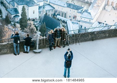 Austria, Salzburg, January 01, 2017: male tourist taking pictures of their friends on the background of attractions. Stroll through the city. Vacation, holidays, attractions.