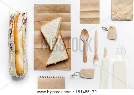 food delivery service workdesk with paper bags and sandwich on white background top view mock-up