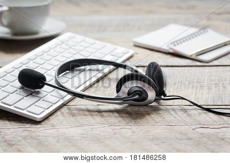 operator headset and computer keyboard on workdesk for call center concept on wooden background