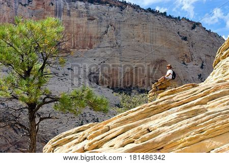 ZION NATIONAL PARK UT - SEPTEMBER 14: Man sits on a rock on Angels Landing in Zion National Park in Utah on September 14 2015