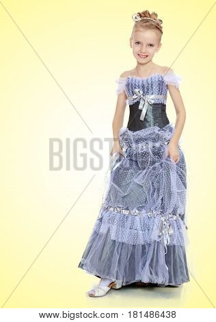 Slender little girl , with beautiful hair on his head, elegant long Princess dress.Girl holding hands to the edge of the dress and put forward a foot to show the shoes.On a yellow gradient background.