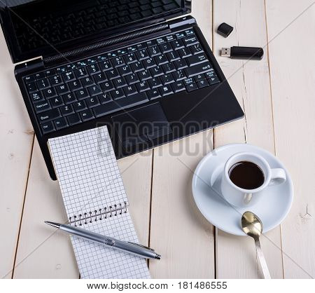 Business still life computer on a wooden table with a cup of coffee and a notebook with a pen.