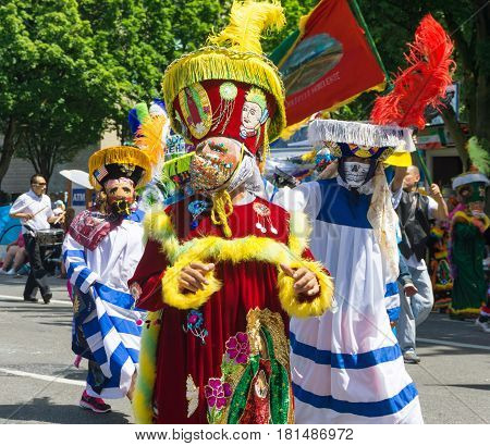 PORTLAND OR - JUNE 6: People dressed in traditional costumes from Mexico as part of the Grand Floral Parade in Portland Oregon on June 6 2015