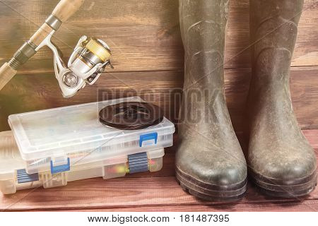 Fishing concept. Fishing tackles in boxes rod reel fishing cage with rubber boots on timber board background. Toned image.