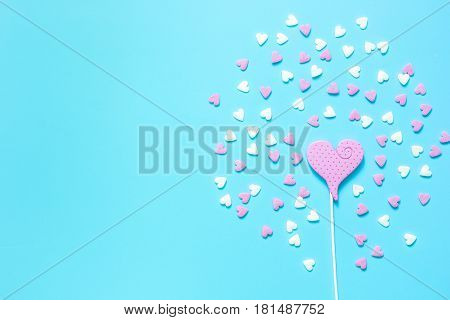 Closeup of a heartshaped lollipop with candy and chewing marmelade on blue table background top view mockup