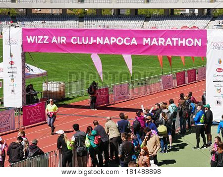 CLUJ-NAPOCA ROMANIA - APRIL 9 2017: Marathon runners compete at the Wizz Air Cluj-Napoca Marathon. Friends and family are following their results from the sides.