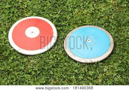 Two girls high school 1K discus on a green grass field
