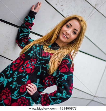 Slanted portrait of Alex as she poses by a zig-zag type modern wall in Liverpool.