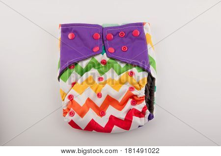 Reusable cloth baby nappy with colorful pattern and pink buttons lay on white background