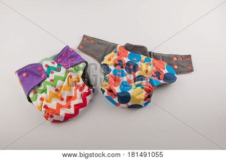 Hygienic colorful washable infant panties with pattern and buttons lay on white background
