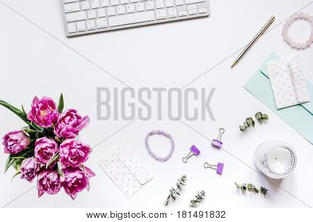 Spring flowers on trendy woman desk in office place on white background top view mock up