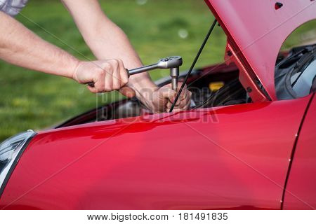 Raised the hood of the car the car remained out of order the master tries to refuse malfunction
