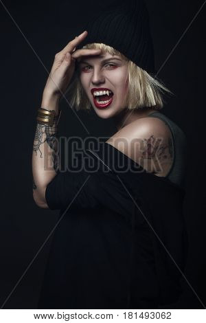 Portrait of vampire woman. Halloween. Studio portrait over black background