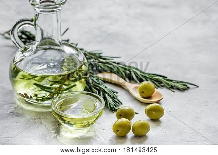 Glass bottle with olive oil and herbs on stone table background mockup