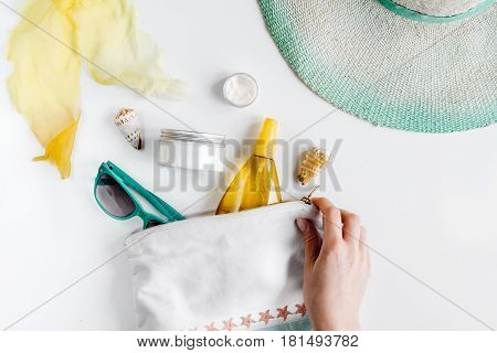 Woman cosmetic set with sun protection lotion and sunglasses and hat for summer seaside rest on white desk background top view