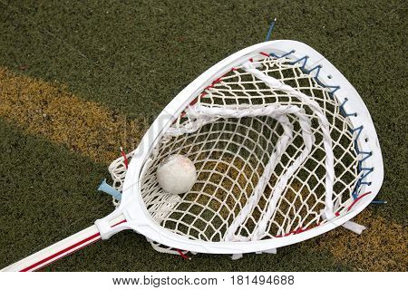 A red and white lacrosse goalie stick on a green turf field with a ball in the net