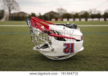 A lacrosse helmet is upside down on a green turf field
