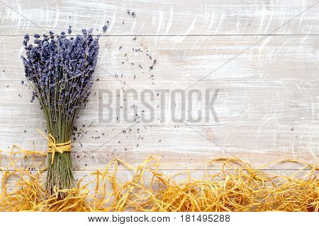 Bunch of dry lavender flowers with straw on rustic desk background top view mock up