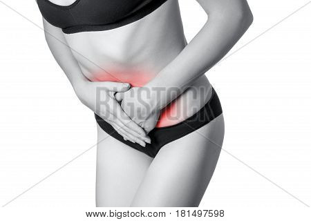 Closeup view of a young woman with stomach pain or digestion or period cycle . isolated on white background. Black and white photo with red dot.