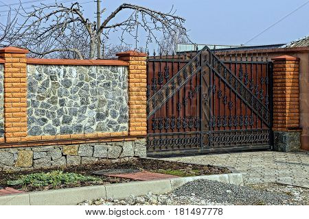 Iron forged doors and a stone fence along the street