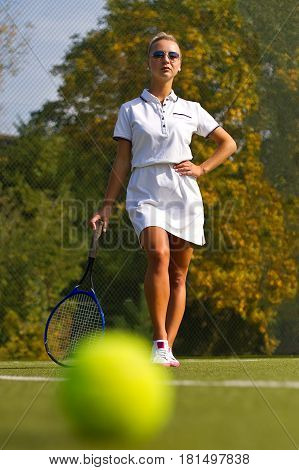 Tennis Ball On The Tennis Court With The Player In The Backgroun
