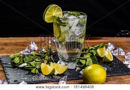 Mojito with mint on wooden table with lime slices, mint