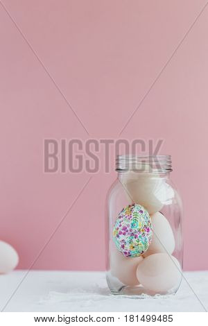 Decorative Egg in Glass Jar with Duck Eggs against Pink Background