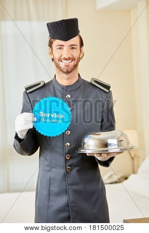 Page with service guarantee badge and food cloche in a hotel room
