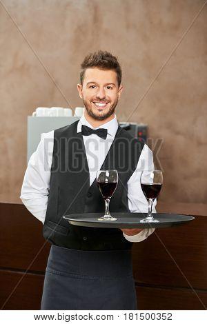 Waiter in uniform serving red wine in a hotel restaurant