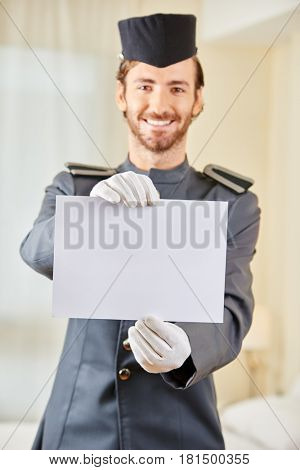 Smiling page in hotel holding a blank white sign