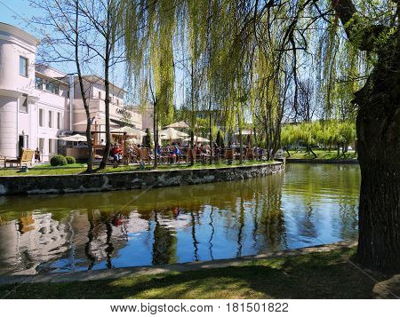 CLUJ-NAPOCA ROMANIA - APRIL 9 2017: Old restaurant building with outdoor terrace near the lake in central park. People relaxing in an idyllic landscape scene.