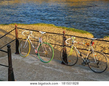 CLUJ-NAPOCA ROMANIA - APRIL 9 2017: Two bicycles lean on a railing by the river at sunset