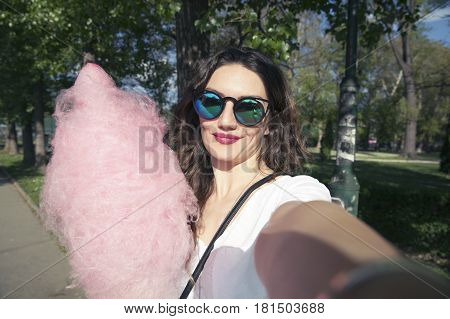 Attractive beautiful young woman with cotton candy taking selfie