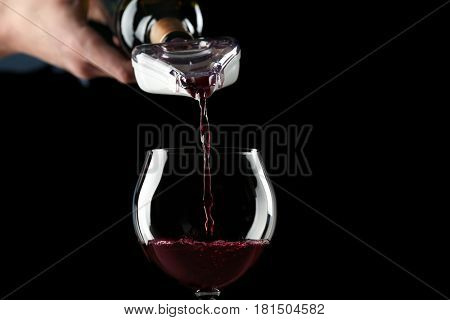 Pouring red wine into glass on dark background