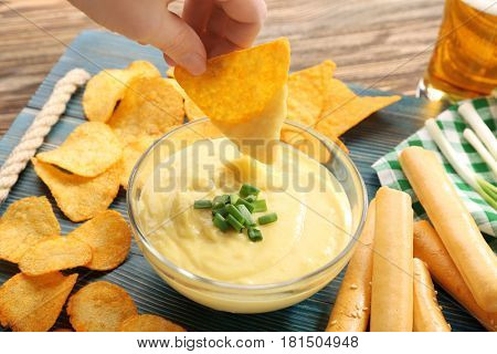 Woman hand dipping nacho in beer cheese dip