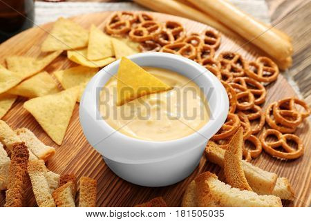 Bowl with beer cheese dip and nacho on wooden stand