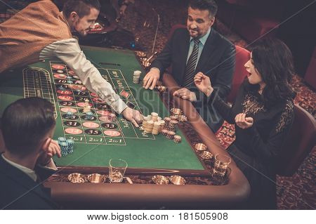 Upper class friends gambling in a casino.