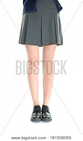 Slender schoolgirl legs in black skirt and leather shoes on white background