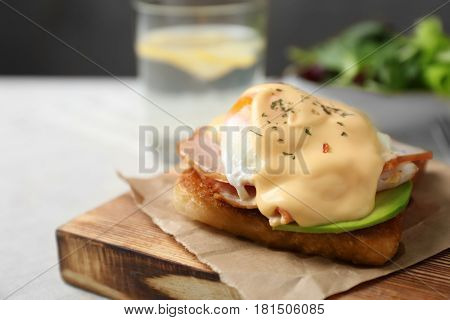Tasty egg Benedict on wooden board